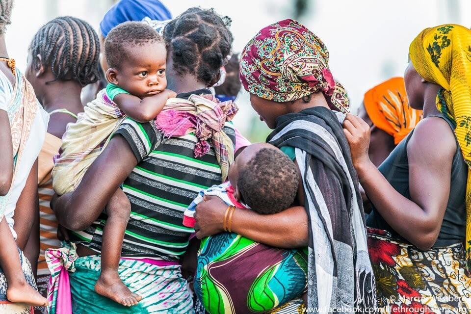 Mulheres amarrando bebés com capulana